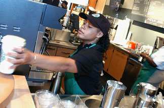 File: A Starbucks Coffee barrista readies a beverage for a customer in the new 42nd Street store August 5, 2003 in New York City.
