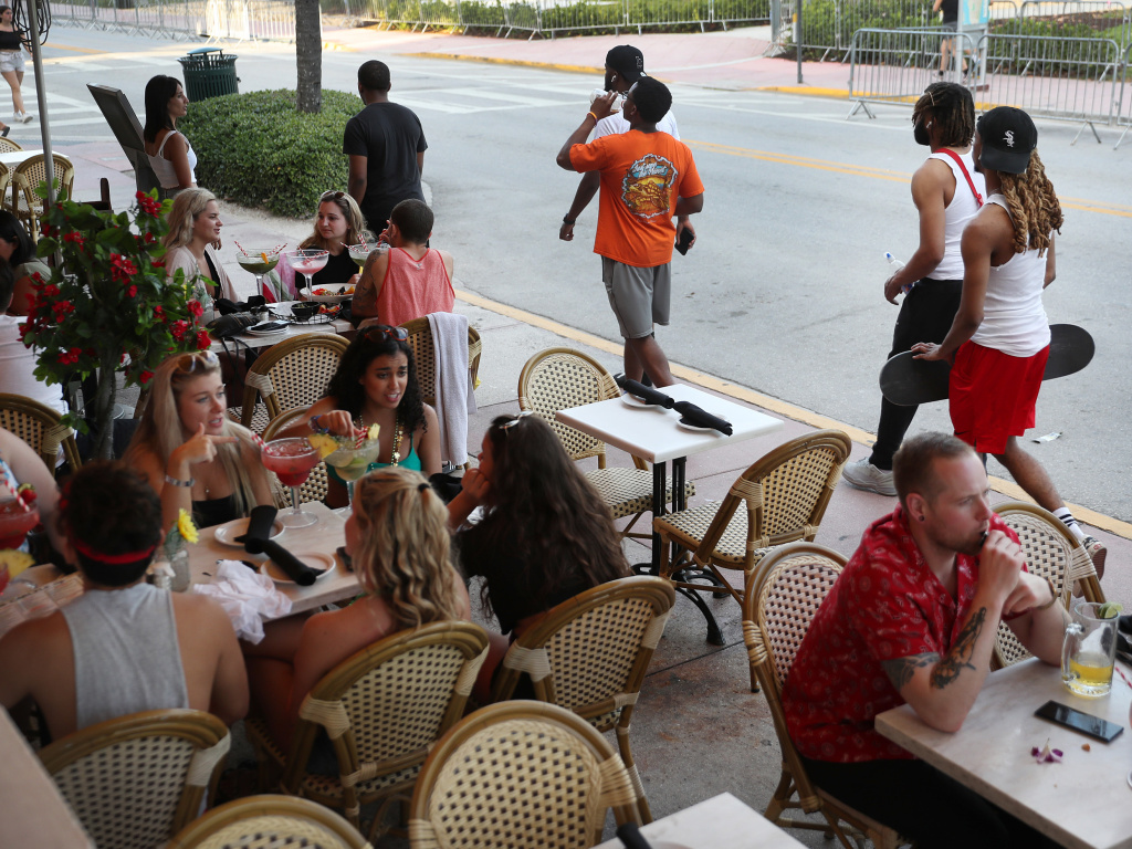 A new analysis finds social distancing has been very effective in slowing the spread of COVID-19 — and that thousands of lives could have been saved if the policies began earlier. In this March 17 photo, people eat at a restaurant along Ocean Drive in Miami Beach, Fla., nearly a week after President Trump declared a national emergency.