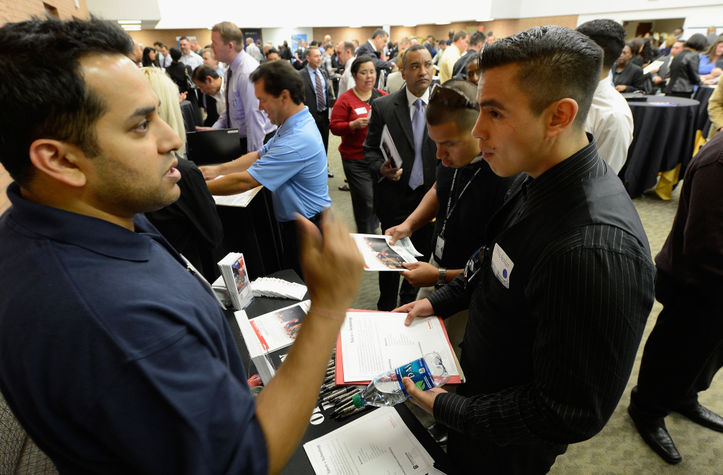 Nicholas Herandez (L), listens to a representative from Raytheon Company during a jobs fair for veterans called
