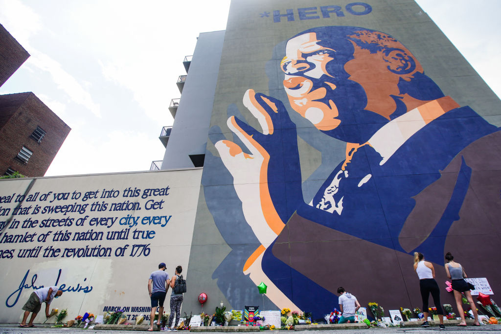 People pay their respects at a makeshift memorial at the base of a mural of Rep John Lewis (D-GA) on July 18, 2020 in Atlanta, Georgia. John Lewis, died at 80 years old,  was an icon leader in the civil rights moment and the Voting Rights Act and served as a United States Congressman for 33 years.