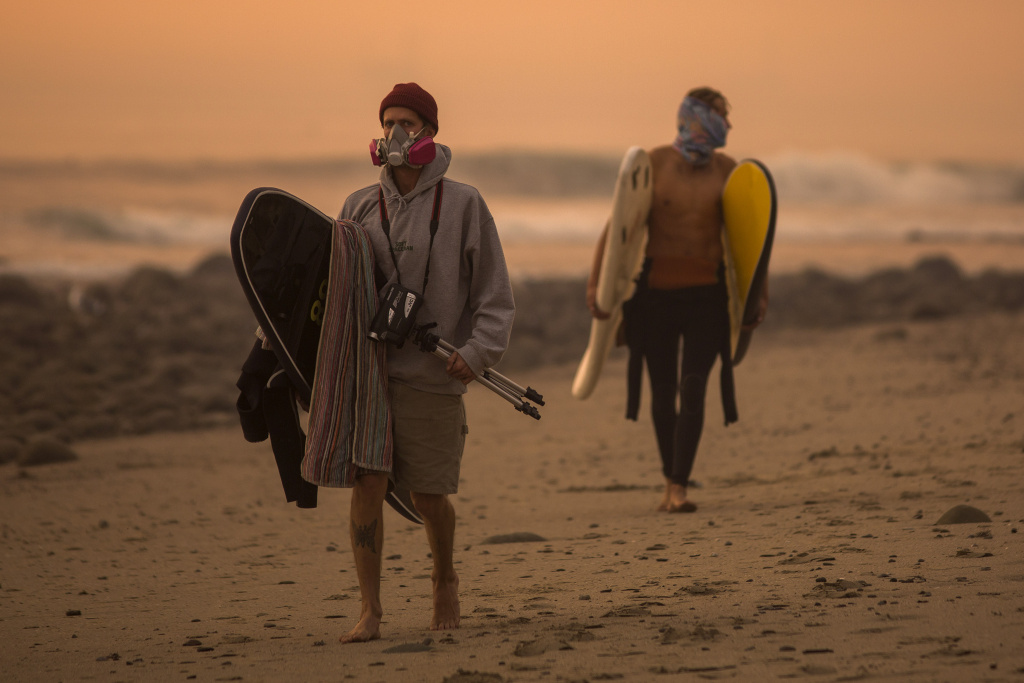Surfers head to the beach under a smoke-filled sky the Thomas Fire continues to burn and threaten communities from Carpinteria to Santa Barbara on December 12, 2017.