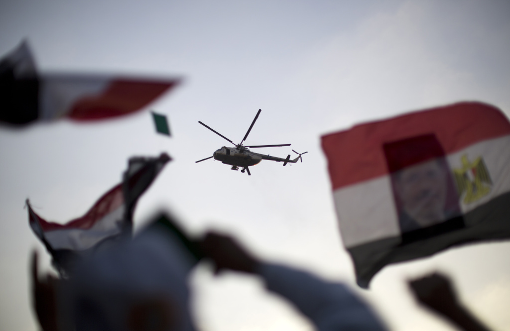 An Egyptian military helicopter hovers over supporters of the Muslim Brotherhood during a rally in support of deposed president Mohamed Morsi outside Cairo's Rabaa al-Adawiya mosque on July 5, 2013.