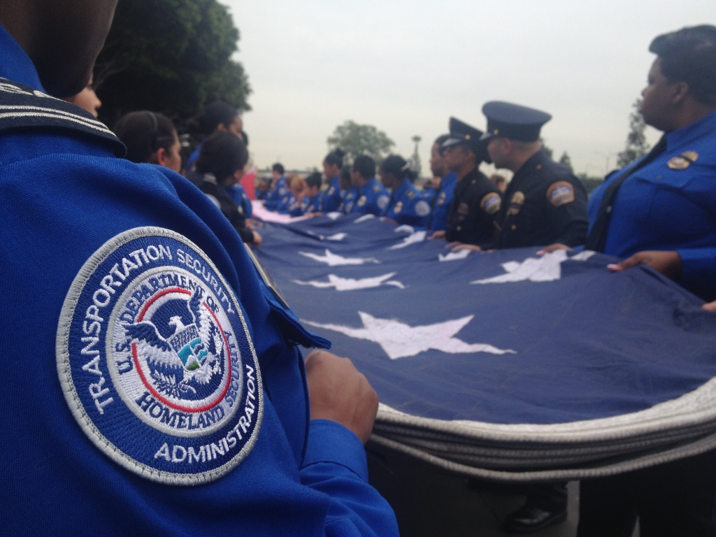 A team of TSA officers and L.A. Airport Police officers fold a traveling honor flag that hung high above the entrance at the memorial held Tuesday for fallen TSA officer Gerardo Hernandez.