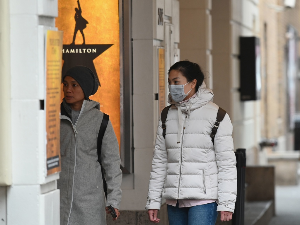 A woman walks past the theater showing <em>Hamilton</em> on Broadway on Thursday in New York City. Audiences won't be seeing the award-winning play for at least a month.