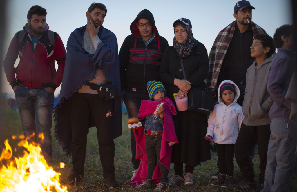 Migrants who crossed the border from Serbia into Hungary last night use a fire to keep warm at dawn at a collection point Tuesday. So far in 2015, more than 367,000 refugees and migrants have crossed the Mediterranean to seek safety and better prospects in Europe, the UN says.