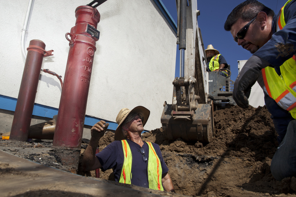 Dan Sapia, left, consults Christopher Cadena while working on a leaking water main at Hoover Street Elementary School. The Los Angeles Unified School District plumbing crew estimated that the repair would take three days. Until the water main feeding the fire sprinklers is fixed, the school has someone on fire watch at all hours of the day.