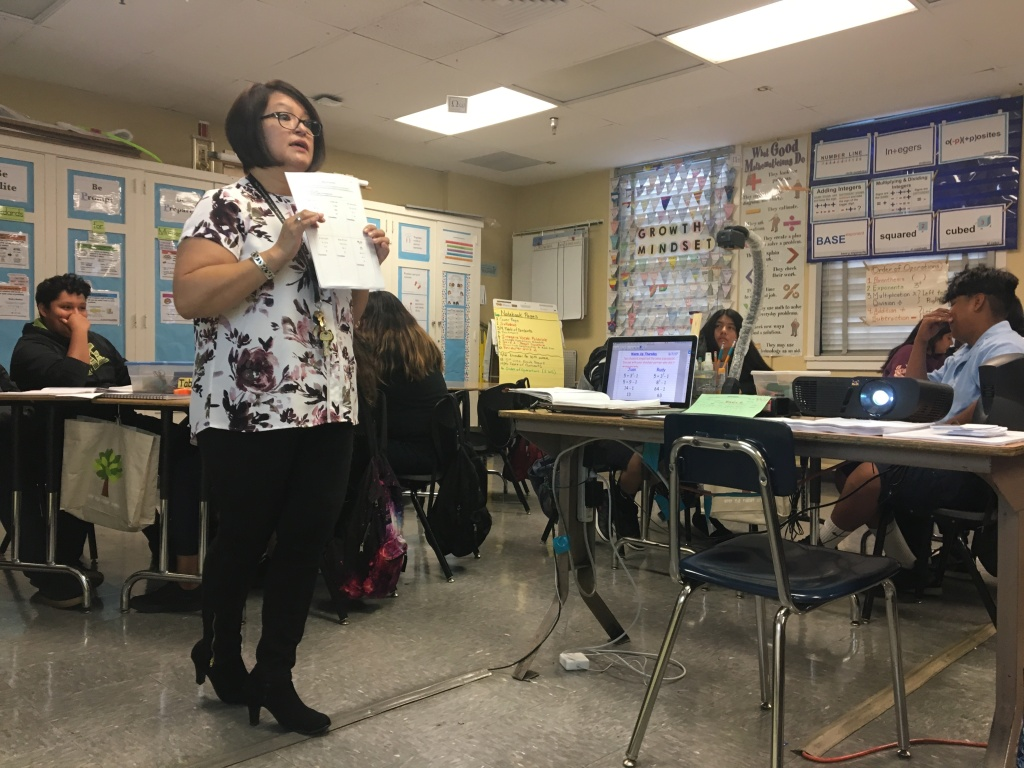 Hollenbeck Middle School teacher Patricia Garibay shows off a worksheet to her math class. After a school-wide shift away from lecturing, she delivers far fewer lectures to her class now than she has done in years past.
