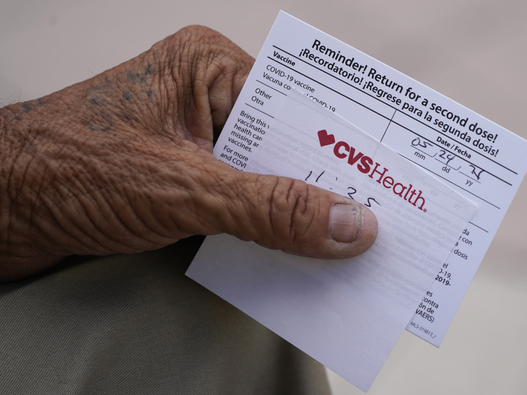 A man holds his vaccination reminder card after having received his first shot at a pop-up vaccination site next to Maximo Gomez Park, also known as Domino Park, on May 3, 2021, in the Little Havana neighborhood of Miami.
