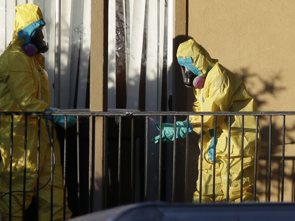 Hazardous material cleaners disinfectant their personal protective equipment after working in the apartment where Thomas Eric Duncan, the Ebola patient who traveled from Liberia to Dallas, had been staying.