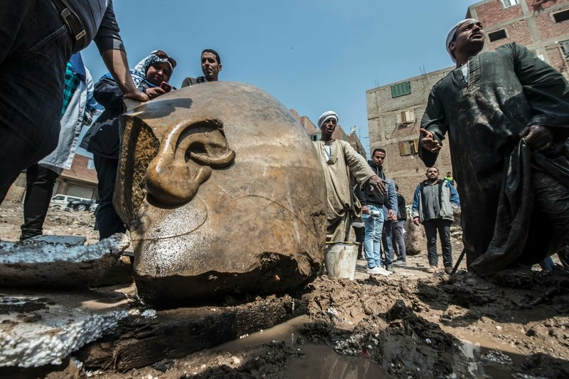Egyptian workers look at the site of a new discovery by a team of German-Egyptian archaeologists in Cairo's Matariya District on Thursday.