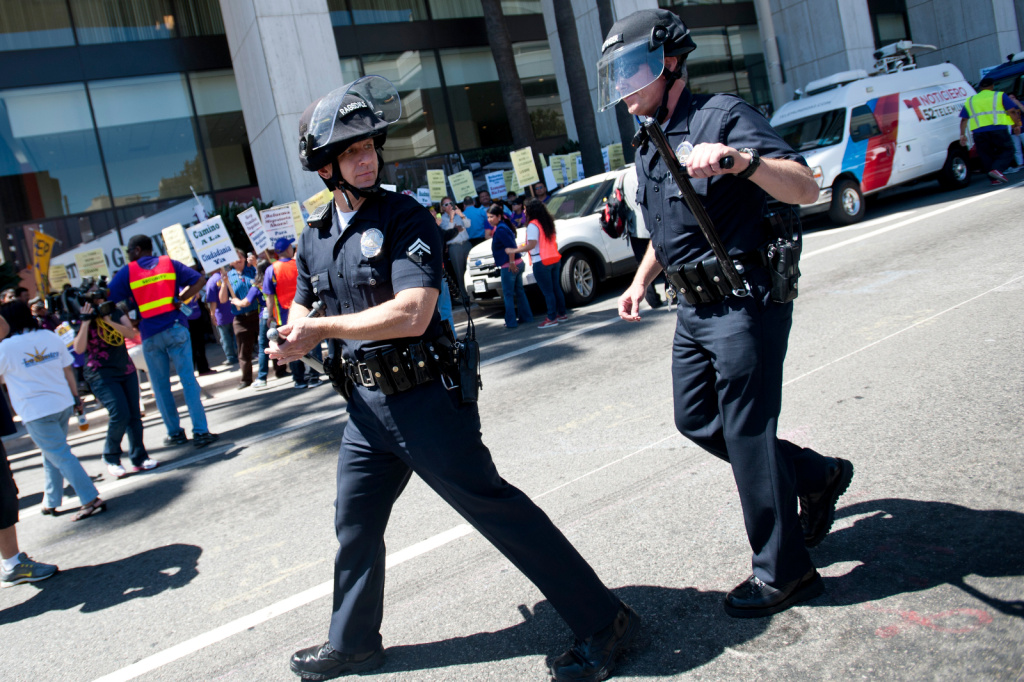LAPD put on helmets, and take a stance around an immigration march.