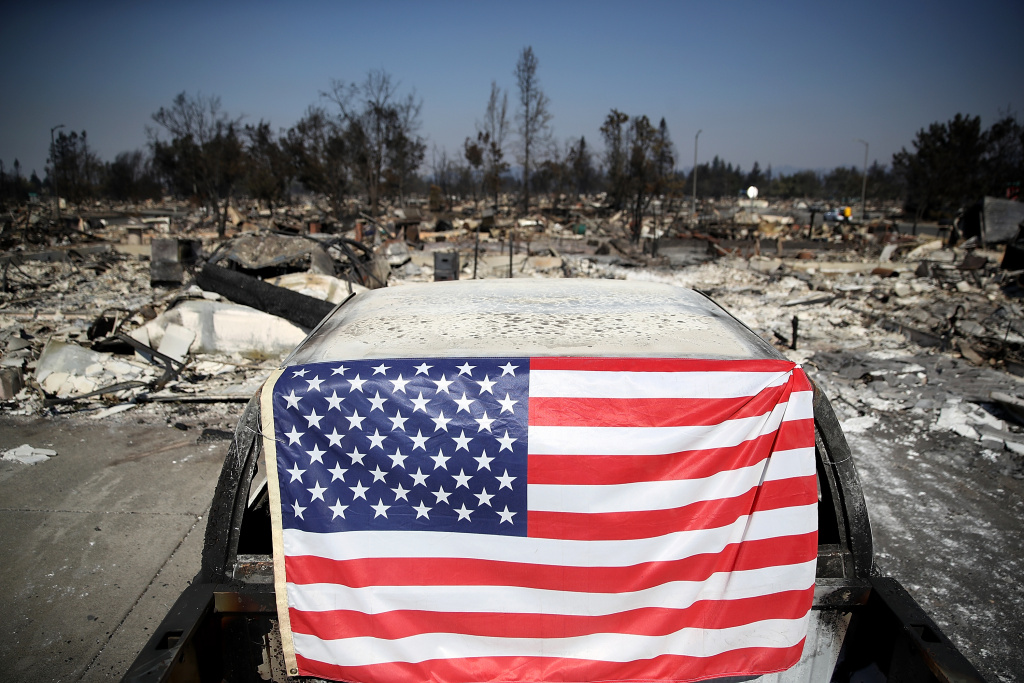 An American flag hangs on a car in front of homes that were destroyed by the Tubbs Fire on October 12, 2017 in Santa Rosa, California.