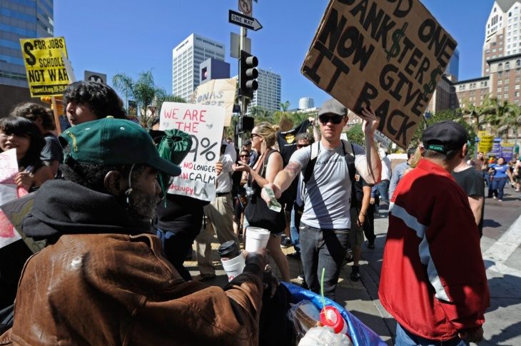 A protester gives money to a homeless man as he marches to Los Angeles City Hall during the 'Occupy Los Angeles' demonstration in solidarity with the ongoing 'Occupy Wall Street' protest in New York City on October 1, 2011 in Los Angeles, California. The protesters slogan, 'We are the 99 percent,' calls attention to the fact that marchers are not part of the 1 percent of Americans who hold a vast portion of the nation's wealth.