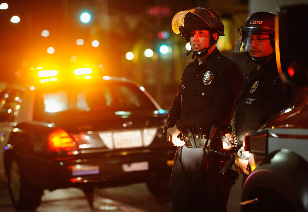 Los Angeles Police Department officers in riot gear look at protestors in the streets around Leimert Park following a prayer vigil against the acquittal of George Zimmerman in the shooting death of Florida teen Trayvon Martin on July 16, 2013 in Los Angeles, California.