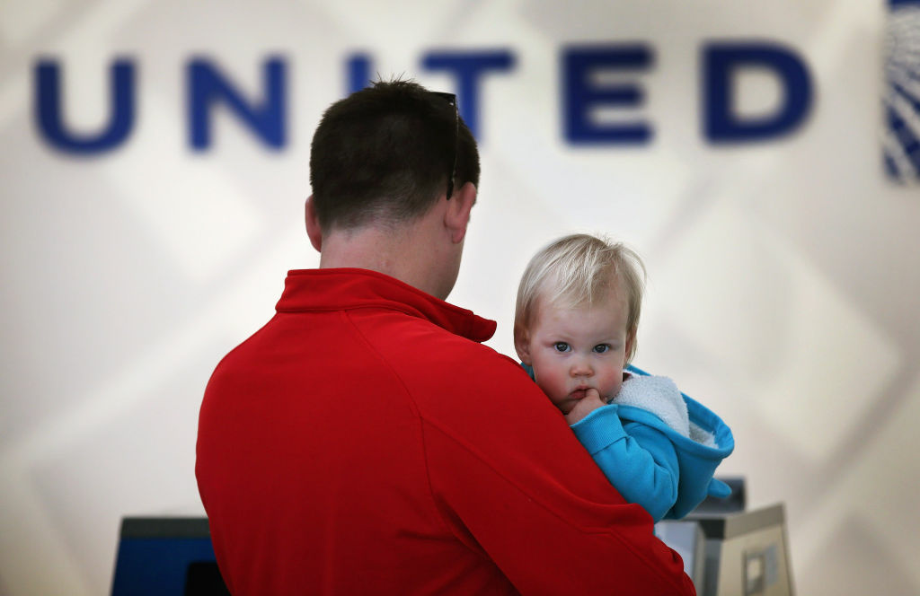 Bill Sanford holds his 14-month-old daughter Clare as he checks in for a flight at O'Hare International Airport. The two were flying to New Jersey to spend the Thanksgiving holiday with family.