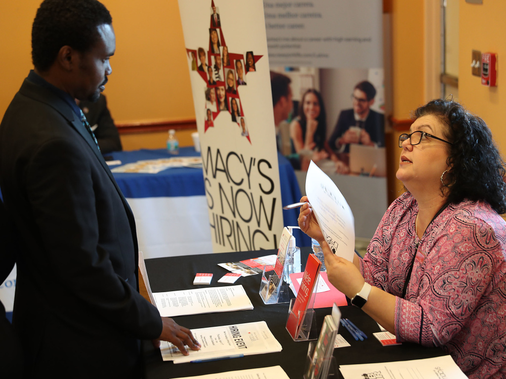 Betty Fernandez of Macy's department store speaks with a potential applicant about job openings during a job fair in Miami on April 5. Analysts expect Friday's jobs report to show that employers continued to add jobs last month.