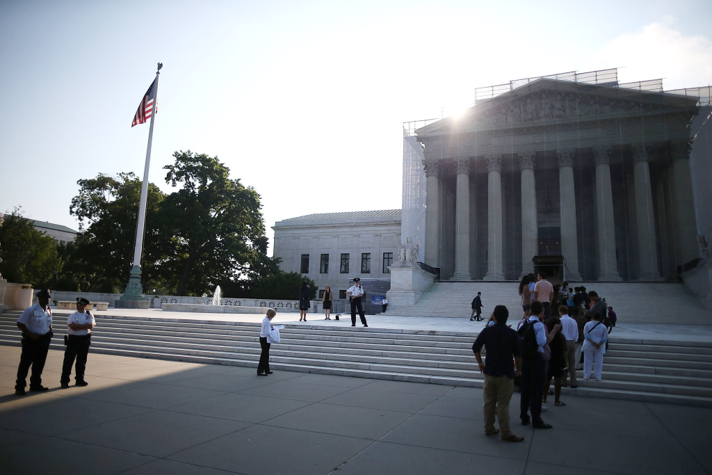 People wait to enter the U.S. Supreme Court building June 24, 2013 in Washington DC.