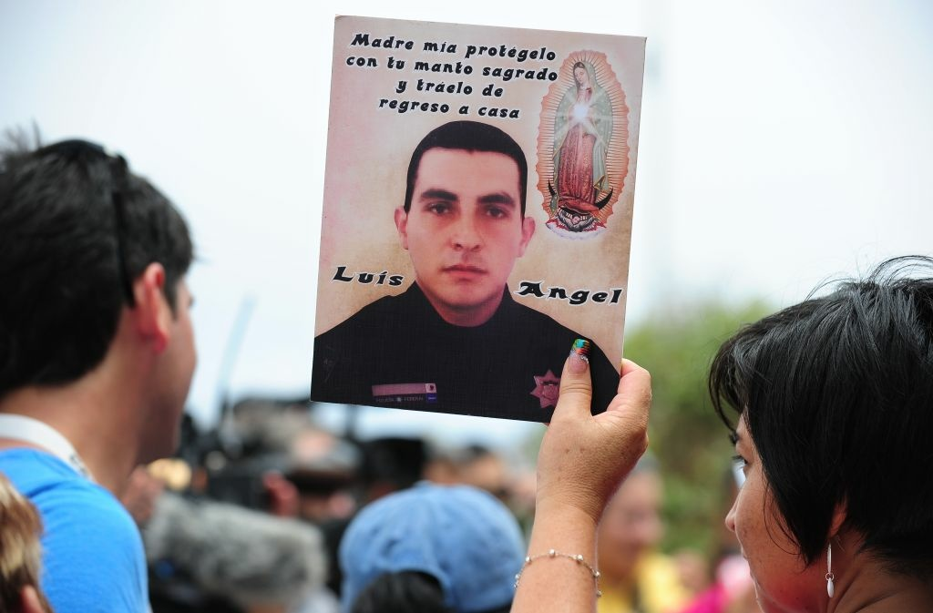 A woman holds a portrait of a deceased or missing loved one as people gather at Border Field State Park, which separates the cities of San Diego and Tijuana, at the US-Mexico border on August 12, 2012 in San Diego, California, to launch 'caravan for peace' across the United States in a month-long campaign to protest the two countries' brutal drug war. The caravan departed from Tijuana with about 250 participants and is due to end in Washington on September 10.