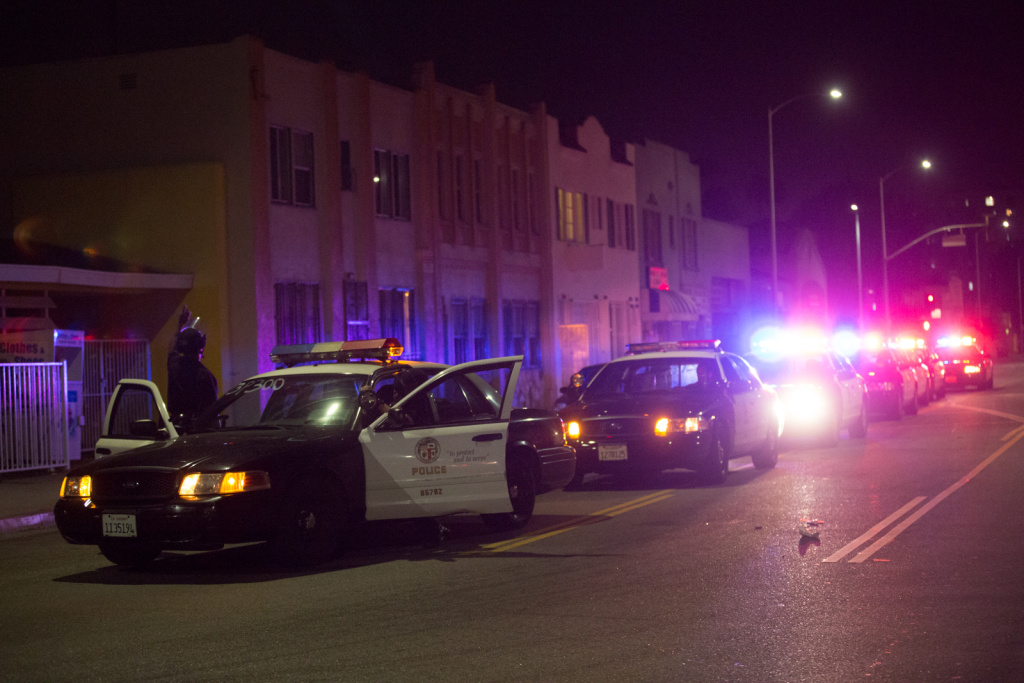Police officers line up on Vernon St. in Leimert Park to take 13 arrested protestors to jail.