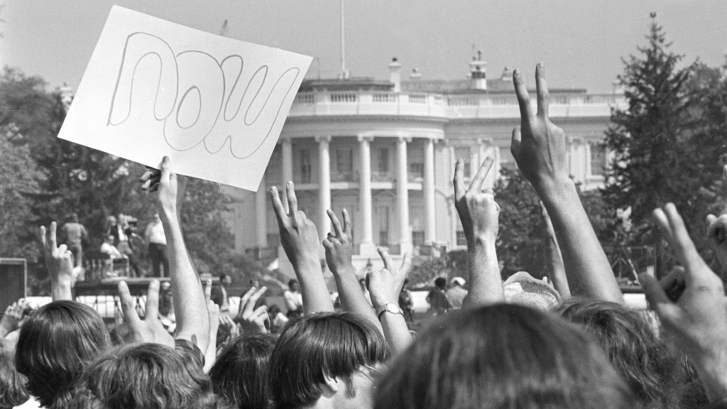 Anti-Vietnam War demonstrators hold up signs and raise their hands toward the White House in a protest. The term