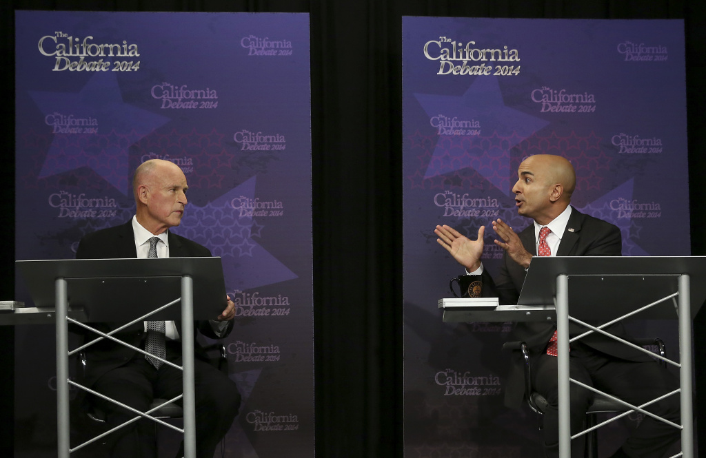 Gov. Jerry Brown, left, listens as Republican challenger Neel Kashkari speaks during a gubernatorial debate in Sacramento, Calif., Thursday, Sept. 4, 2014. Thursday's debate is likely to be the only one of the general election.