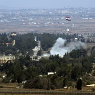 Smoke rises near a Syrian flag hoisted up a flagpole as a result of the fighting between Syrian rebels and the Syrian Army over the control of Quneitra crossing, on Saturday. The area is where  dozens of U.N. peacekeepers had been under siege by Nusra Fro