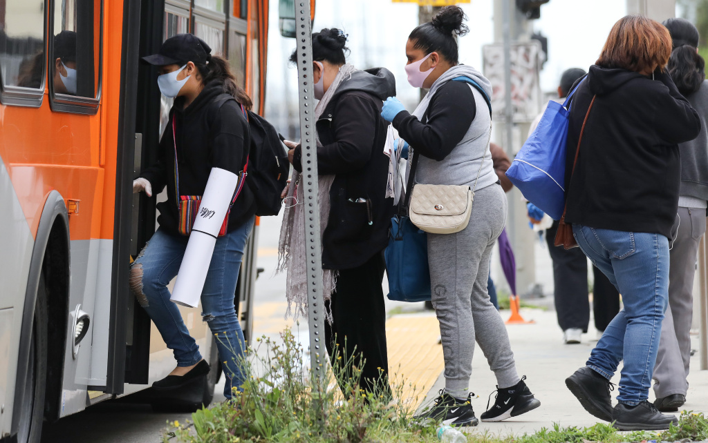 People board a bus wearing face masks amid the coronavirus pandemic on April 6, 2020 in south Los Angeles, California. Nearly 11,000 people have died in the U.S. from COVID-19.