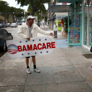 Pedro Rojas holds a sign directing people to an insurance company where they can sign up for the Affordable Care Act, also known as Obamacare.