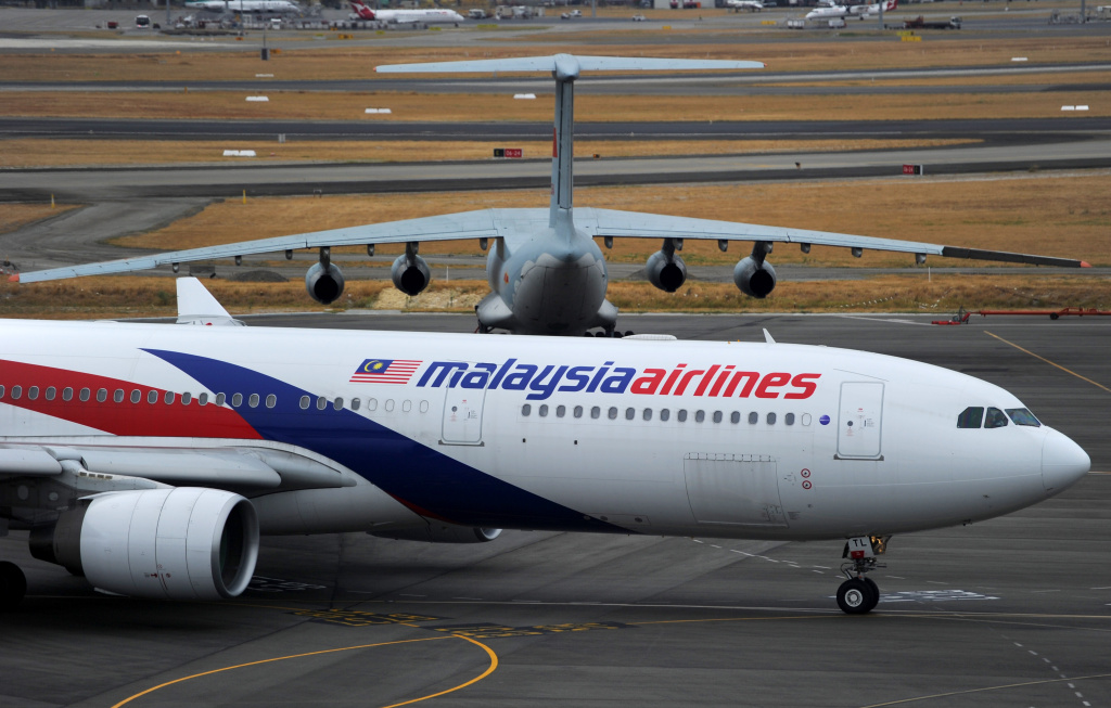 A Malaysia Airlines plane prepares to go out onto the runway and passes by a stationary Chinese Ilyushin 76 aircraft (top) at Perth International Airport on March 25, 2014 in Perth Australia.
