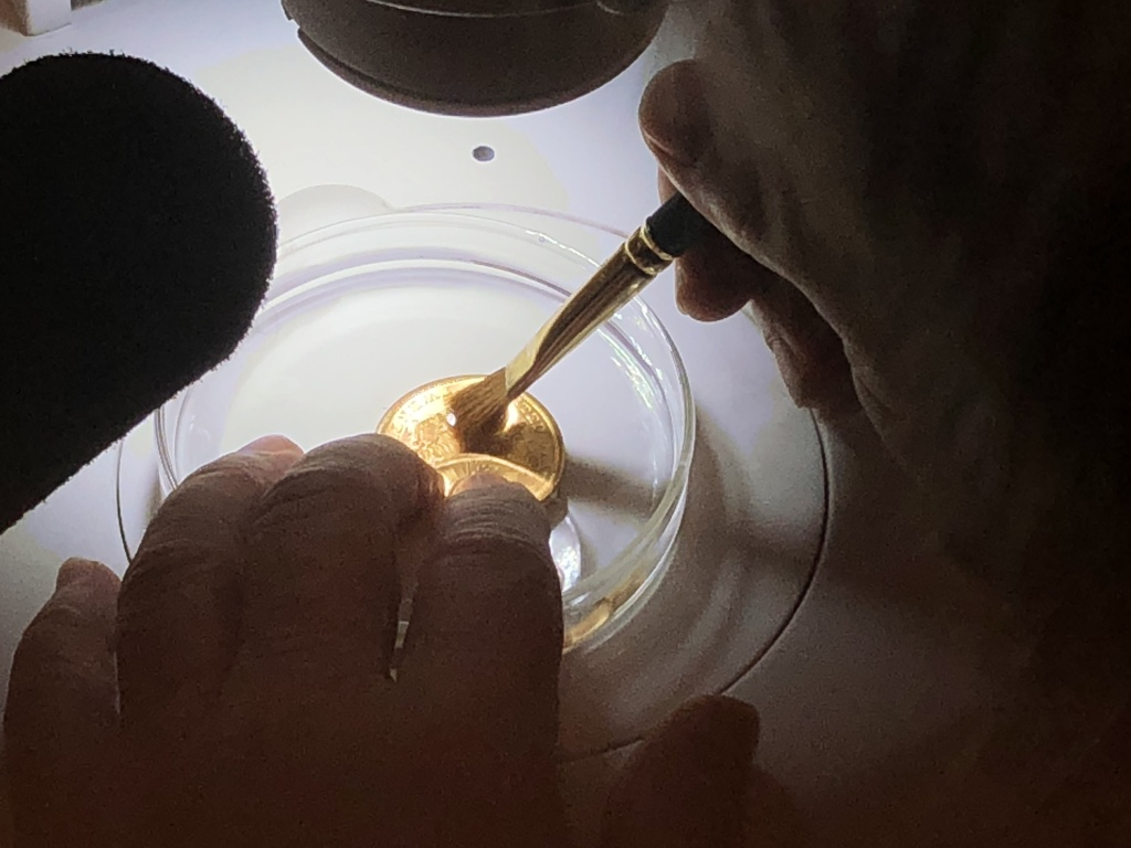 Bob Evans works with an artist's brush under a microscope to ensure each coin is spotless