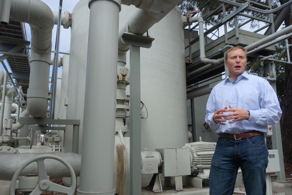 File: In this April 25, 2014 photo, Joshua Haggmark, interim resources manager for Santa Barbara, stands next to a desalination plant, which removes salt from ocean water.