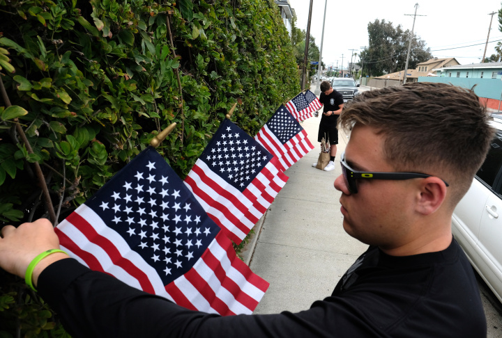 U.S. Marine PFC Joseph Dudley, foreground, with PFC Zak Stepniewski, place American Flags in an ivy-covered wall next to a vandalized war memorial in Venice Beach on Monday, May 30, 2016. The two Marines on leave from their base in Twentynine Palms left 100 American flags there Monday until it can be restored.