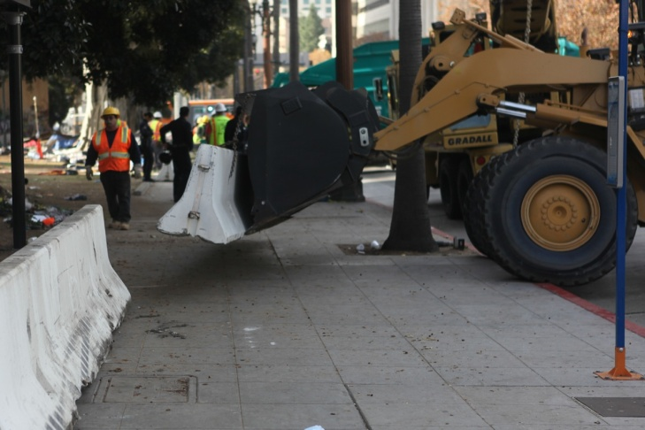 A sanitation worker cleans up the site of the Occupy Los Angeles camp Wednesday morning following the protesters' removal.