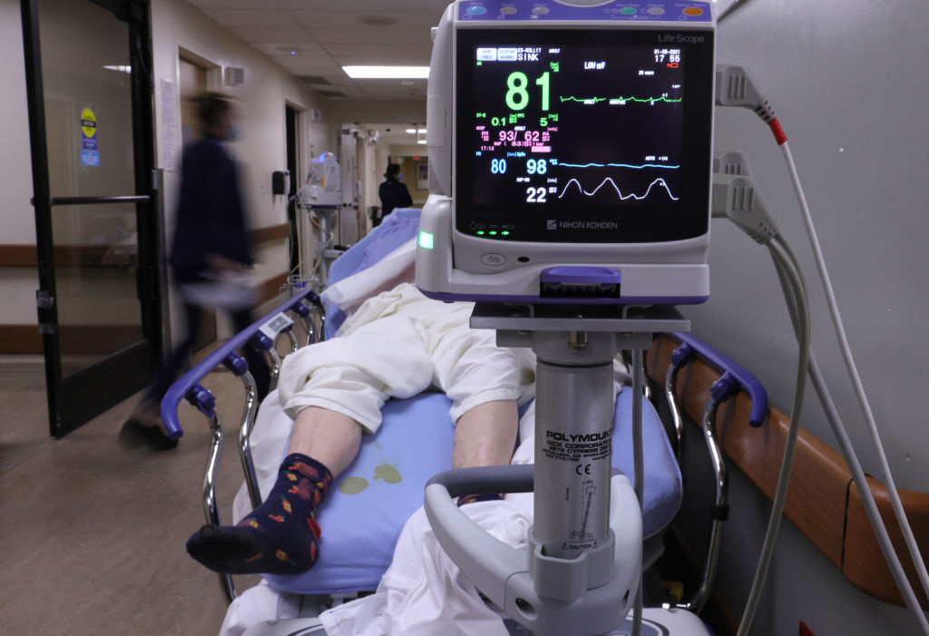 A patient lies on a stretcher in a hallway in the overloaded Emergency Room at Providence St. Mary Medical Center amid a surge in COVID-19 patients in Southern California on January 5, 2021 in Apple Valley, California.