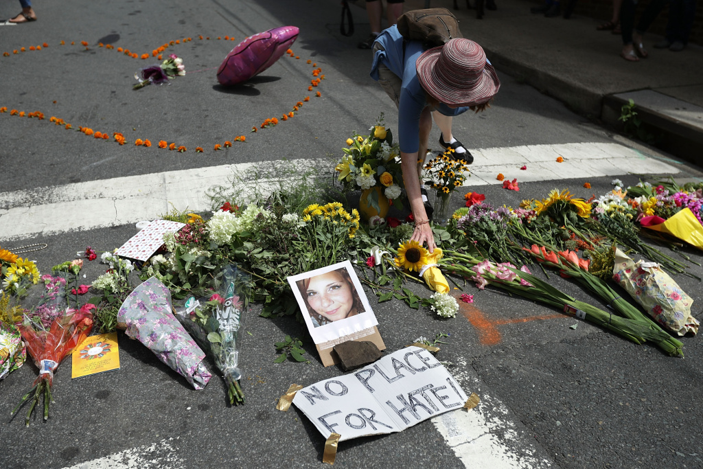 CHARLOTTESVILLE, VA - AUGUST 13:  A woman places flowers at an informal memorial to 32-year-old Heather Heyer, who was killed when a car plowed into a crowd of people protesting against the white supremacist Unite the Right rally, August 13, 2017 in Charlottesville, Virginia. (Photo by Chip Somodevilla/Getty Images.)