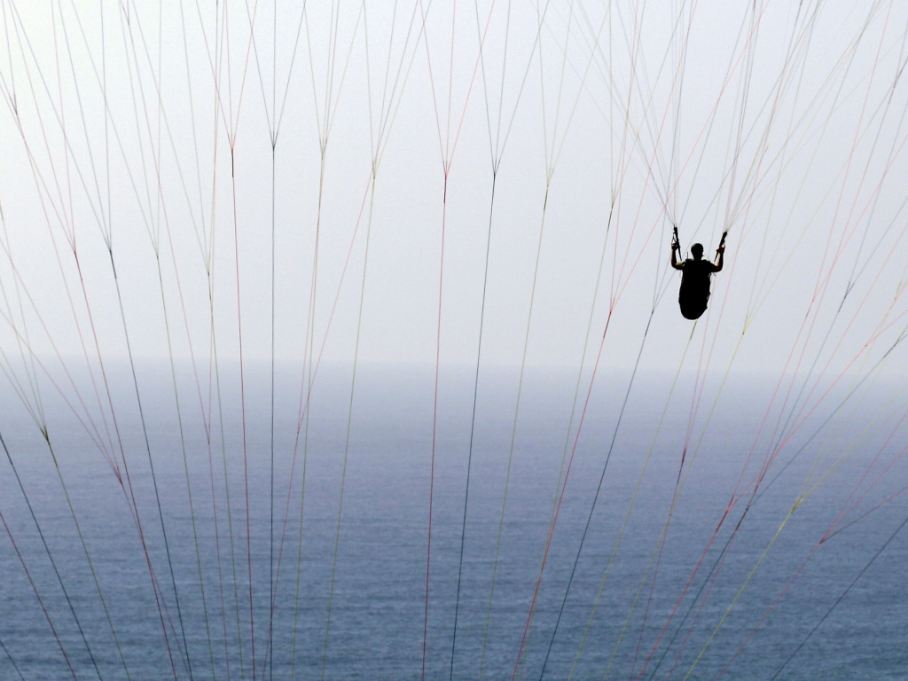 In this 2012 photo, a man paraglides behind the lines of another paraglider off the Torrey Pines Gliderport in San Diego.