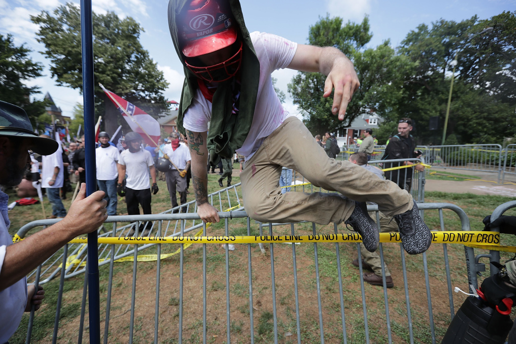 White nationalists, neo-Nazis and members of the alt-right leap over barricades inside Lee Park during the