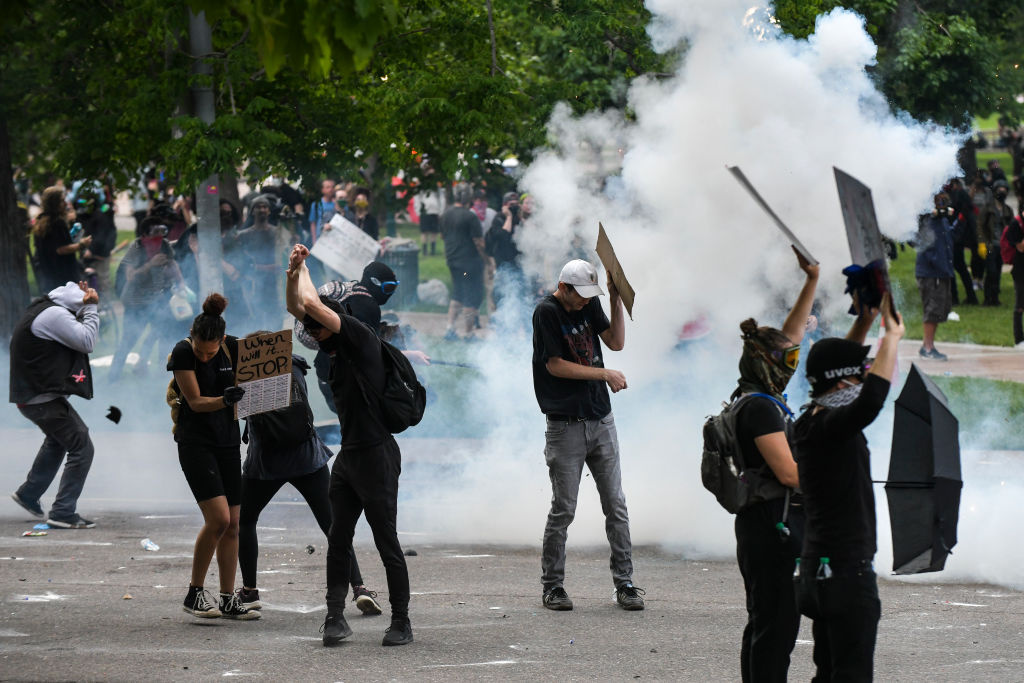 People react as police officers discharge tear gas next to the Colorado State Capitol as protests against the death of George Floyd continue for a third night on May 30, 2020 in Denver, Colorado.