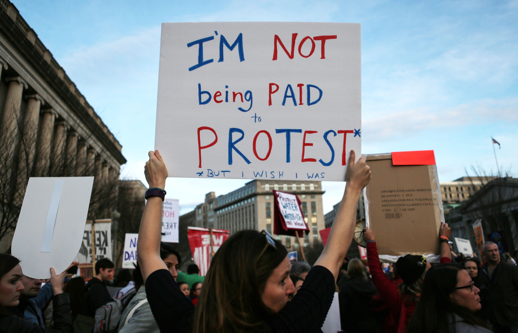 A demonstrator holds a sign reading 'I'm not being paid to protest