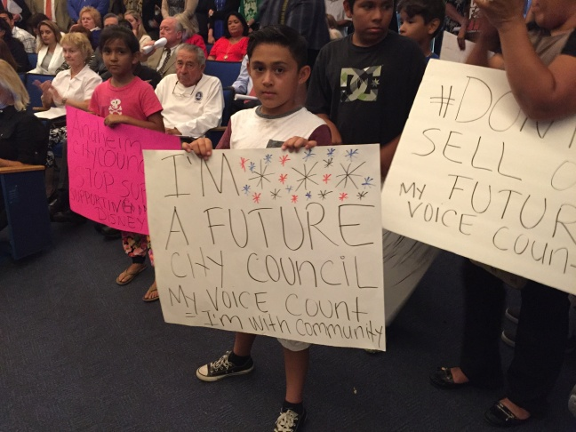 Oscar Borrayo, 8, holds up a sign at the Anaheim City Council meeting on the proposal to shield Disney from admission taxes for 30 more years in exchange for a $1 billion investment in the parks and surrounding streets.