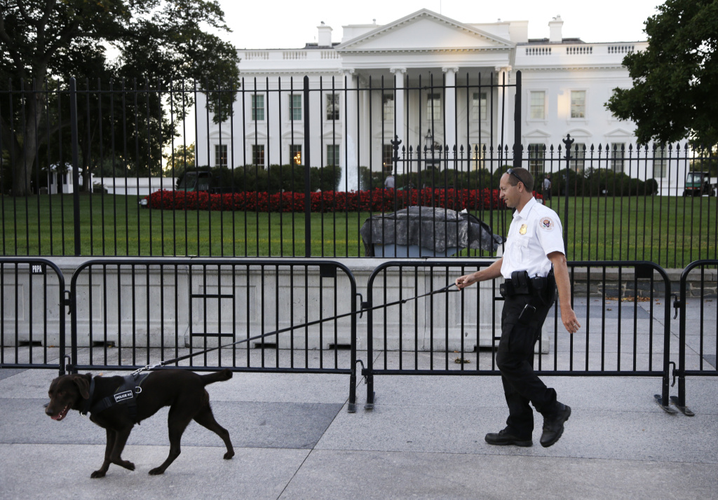 A member of the Secret Service Uniformed Division with a K-9 walks along the perimeter fence along Pennsylvania Avenue outside the White House in Washington, Monday, Sept. 22, 2014. The Secret Service tightened their guard outside the White House after Friday's embarrassing breach in the security of one of the most closely protected buildings in the world. A man is accused of scaling the White House perimeter fence, running across the lawn and entering the presidential mansion before agents stopped him. (AP Photo/Carolyn Kaster)