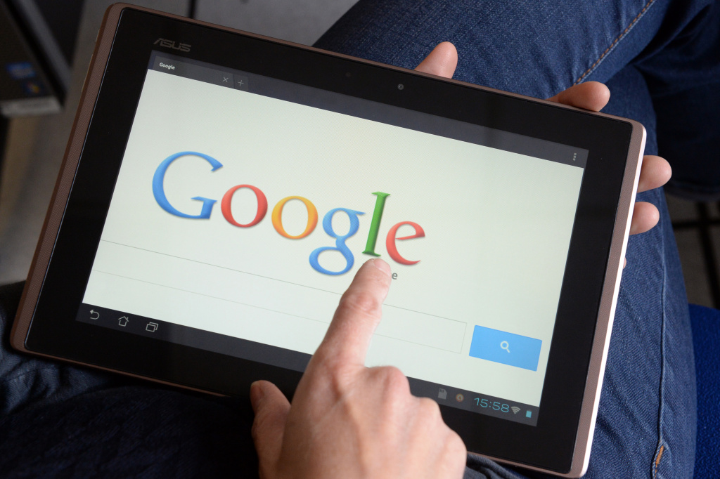 A woman chooses Google Search web search engine front page on her tablet.
