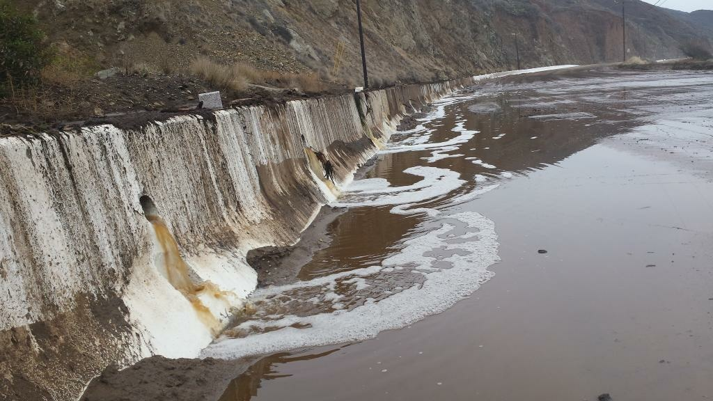 Water and mud cover Pacific Coast Highway north of Deer Creek Road after Sunday's rains forced its closure.