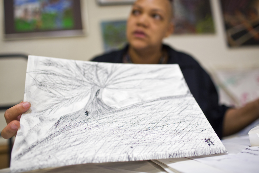 Mykael Williams-Wolf holds a piece he made with loose charcoal. LAMP's arts program first started in 1999 and is aimed towards creating a creative space for people who are homeless, living in extreme poverty or have a mental illness.