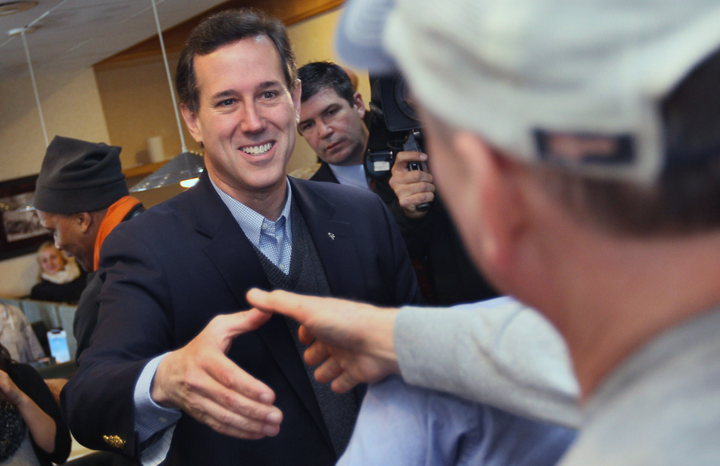 GRANDVILLE, MI - FEBRUARY 28: Republican presidential candidate and former U.S. Sen. Rick Santorum (R-PA) (L) greets diners at the Rainbow Grill on February 28, 2012 in Grandville, Michigan.