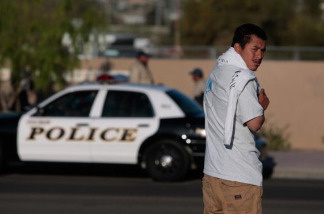 A day laborer looking for work turns away from a police car Tucson, Arizona. A House panel has approved a strict immigration enforcement bill that among other things would let state and local governments set their own immigration policies, and give state and local cops greater latitude to enforce immigration laws.