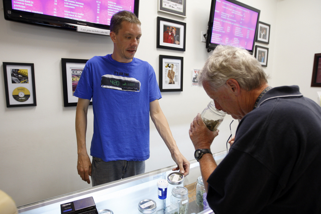 Reed Moran smells a variety of marijuana shown to him by President and CEO Sam Humeid (L) of the Perennial Holistic Wellness Center medical marijuana dispensary, which opened in 2006, on July 25, 2012 in Los Angeles, California