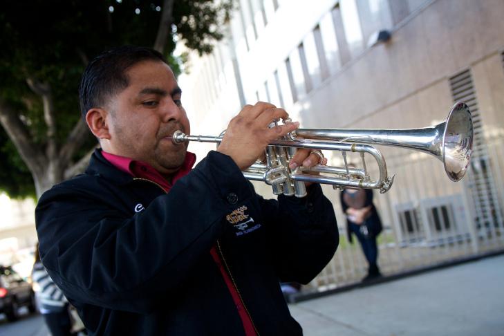 A band member named Jesus plays along to Feliz Navidad outside the Metropolitan Detention Center today, December 21, 2011.