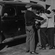 Police officers are shown on the way to court with a group of Mexican youth who assertedly took part in a gang war in which a 17-year-old boy suffered bullet and stab wounds. The youth were scheduled for arraignment on this day, Tuesday, March 27, 1945.