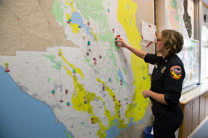 Cal Fire Capt. Leah Simmons-Davis moves magnets on a map representing firefighters. On the night of Oct. 8, Cal Fire staff ran out of magnets for fires, so crews had to start using Post-its.